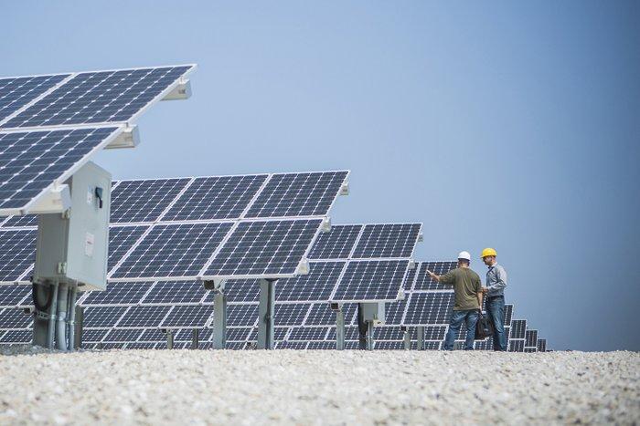 solar technicians talking near solar panels