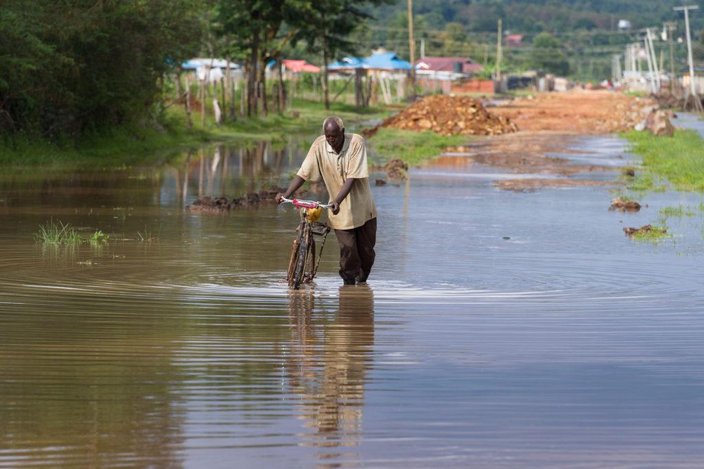 Man wading through flood water outside Nairobi, Kenya, 13 January 2020. Credit: Alex MacNaughton / Alamy Stock Photo. 2B5GMJ9