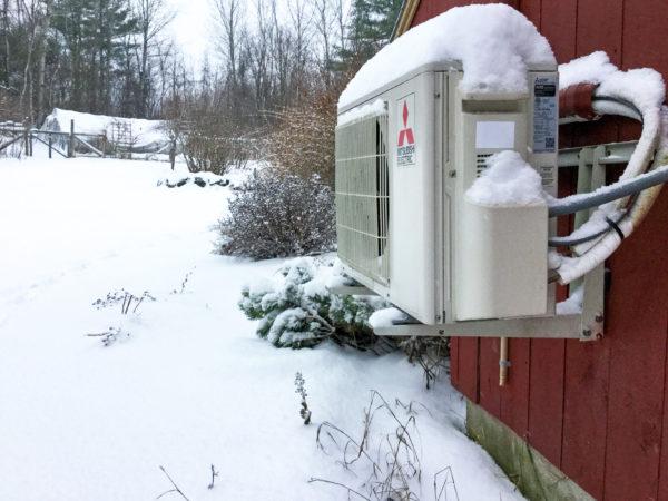 Mitsubishi air source heat pump outdoor unit at snowy Canterbury, NH home